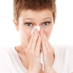 woman holding a tissue to her nose