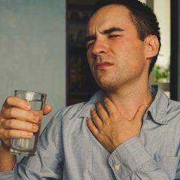 A parched throat and a glass of water in hand with an expression of pain