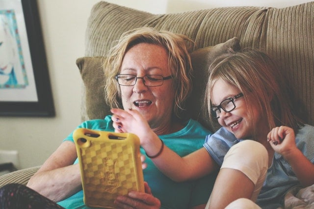 woman and young girl sitting in a recliner while playing with a tablet
