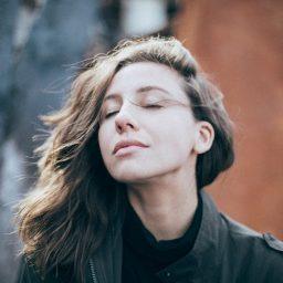 Woman taking deep breath outside.